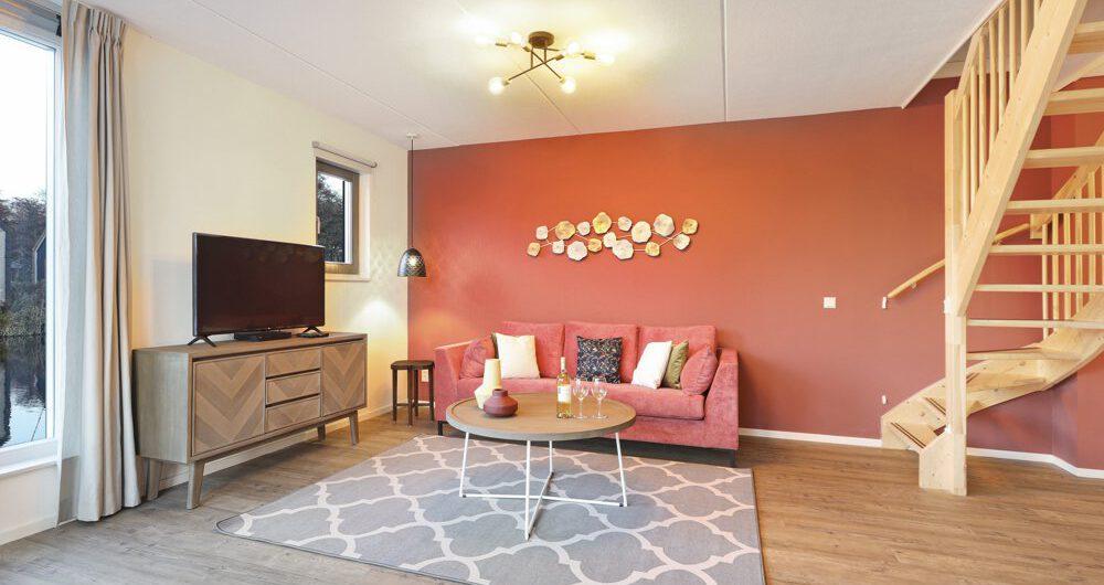 Woonkamer met tomatenrode achterwand in de woonkamer in een van de vakantiehuizen van Landal