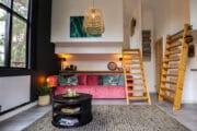 Woonkamer met roze bank en trapjes naar de vides