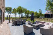 Groot terras met loungebanken en eethoek