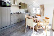 Keuken met een ronde eettafel en taupe keukenkastjes