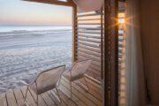 Ondergaande zon schijnt naar binnen in het strandhuis