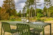 Groen tuinmeubilair met fles wijn en glazen op tafel, uitzicht op de Drentse natuur