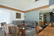 Ruime woonkamer met lange eettafel en hoekbank