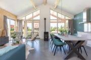 Ruime woonkamer met grote ramen, in het vakantiehuis in Friesland