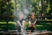 Kinderen bij een vuurtje bij een vakantiehuis in het bos